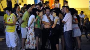 Pendant les JO de Pékin, un groupe regarde la cérémonie d'ouverture sur un téléphone mobile